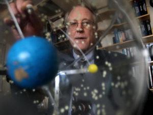 Professor Richard Binzel looking through an orrery
