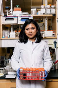 Graduate student holds a case of vials in a lab.