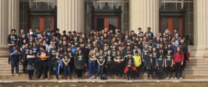 Over 100 middle school students in matching green shirts and adults in matching blue shirts stand on stone steps in front of building with large columns