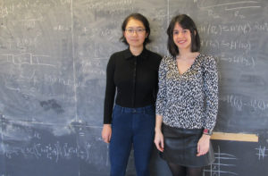 Two women stand in front of chalk board covered in equations.