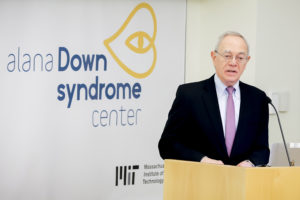 man at podium in front of Alana Down Syndrome Center sign