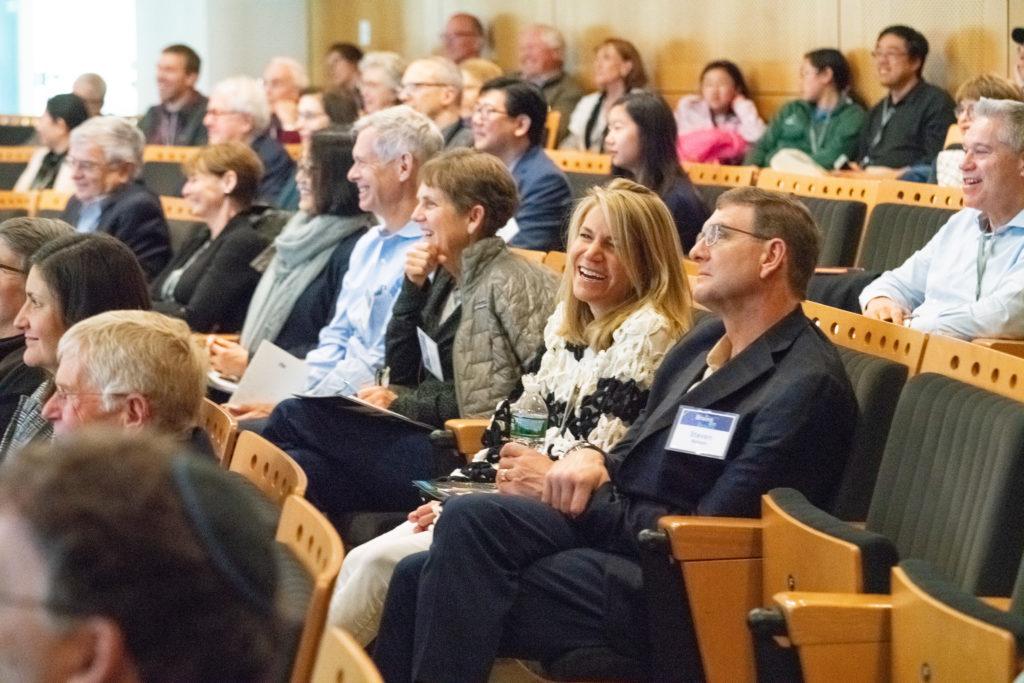 Audience members watching presentations