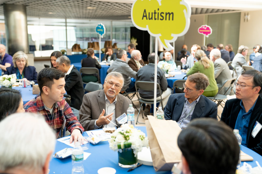 "several people chat at a table with an ""Autistm"" sign"