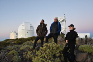 two men and a woman stand on a hill looking off into the distance with a white observatory behind them