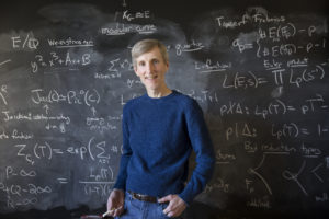 man in front of a chalkboard covered in equations