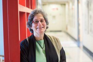Susan Solomon leans against a corridor wall