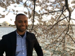 Thomas Searles in front of some cherry blossoms